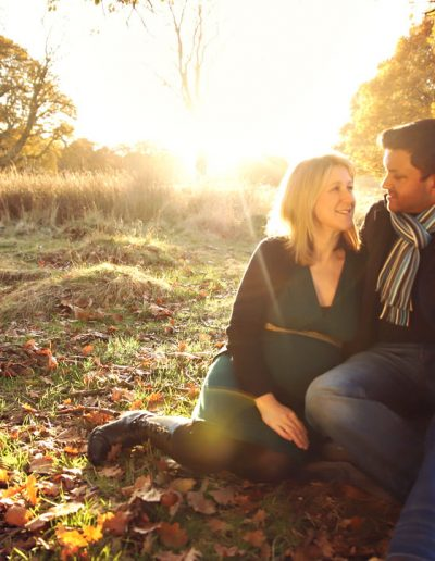 Ania Chandra maternity Photographer in Reading and beyond. Photo of pregnant mama with her husband sitting down on the tree during sunset in Richmond Park in London. They look in love and very happy looking at each other