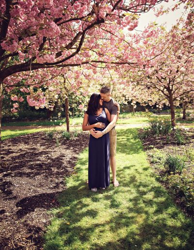 Ania Chandra Photography in Berkshire, Reading Harris Garden. Cape are standing under the blossom tree and holding each other with love. Mama is pregnant and happy