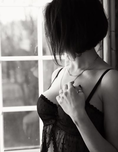 women standing next to the window in her lingerie - looking outs so that you van not see her face - but you can see her hand and decode - boudoir image done by Ania Chandra photographer in Reading - Black and white image