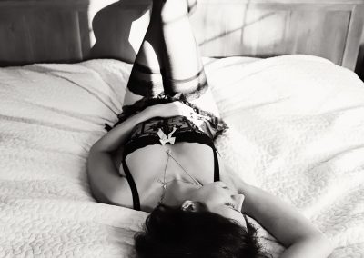 Ania chandra photographer in Reading - Boudoir photo of women lying on the bed with legs up looking sexy and beautiful