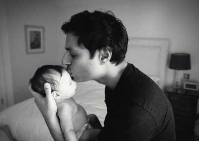 reading newborn photographer - father holding and kissing baby - ania chandra photography