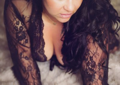 Boudoir photographer Ania Chandra in Reading - beautiful curvy women with black hair is sitting up on the bed with her hands down