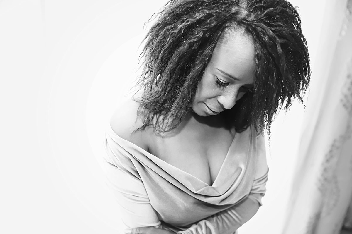 black women and a mother looking  down and she has off the shoulder dress - she looks glam and elegant - Boudoir Black and White image by Ania Chandra photographer in Reading