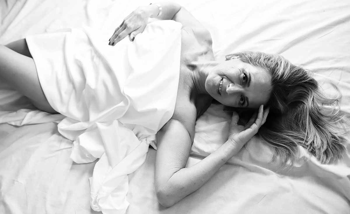 women in her 60s is lying down on her back on the whiite sheet covered with the white sheet too - she is smiling and she looks very confident and beautiful - image done by Ania Chandra Photography Boudoir